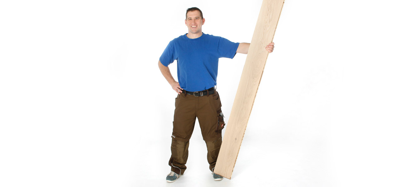Andreas Goedicke, Parkettlegermeister Frontalaufnahme in Arbeitskleidung mit Holzdiele in der Hand